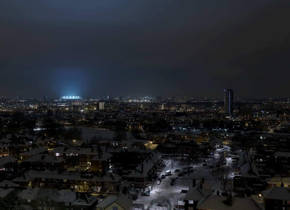 Londons Olympic Stadium lights up for the first time as snow falls across the city
